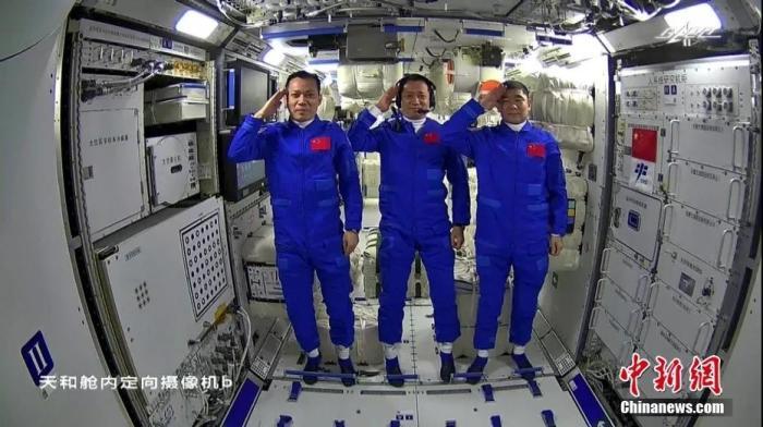 资料图:进入空间站后,三名航天员向全国人民报告并致谢敬礼。(视频截图)图片来源:视觉中国