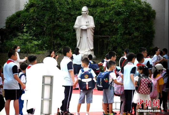 资料图:某小学,学生经过校园里的孔子雕塑并鞠躬。王东明 摄