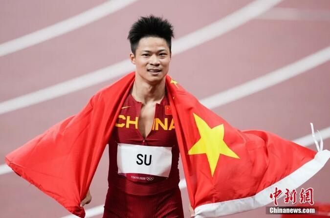 在东京奥运会男子百米决赛中,中国选手苏炳添以9.98秒的成绩获得第六名。图为苏炳添在赛后身披国旗。图片来源:视觉中国
