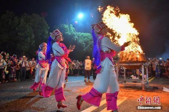 """资料图:云南省石林彝族自治县举办火把狂欢节,上万名游客和当地民众一起点起火把,围着篝火载歌载舞,度过有""""东方狂欢节""""之称的火把节。中新社记者 任东 摄"""