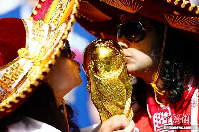 资料图:俄罗斯世界杯1/8决赛西班牙对阵俄罗斯的比赛即将进行。赛前,俄罗斯球迷亲吻大力神杯。<a target='_blank' href='http://www.chinanews.com/'>中新社</a>记者 富田 摄