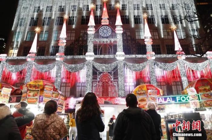 资料图:美国传统节日感恩节,纽约第五大道一家商场布置节日灯光秀吸引民众驻足观看。中新社记者 廖攀 摄
