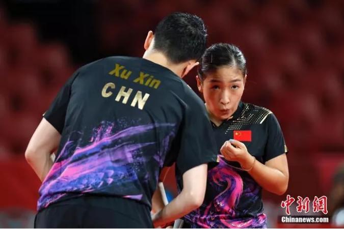 7月26日,东京奥运会决出了乒乓球项目的首枚金牌。在混双决赛中,中国组合许昕/刘诗雯在先胜2局的情况下遭遇逆转,以3:4惜败日本组合水谷隼/伊藤美诚。图为刘诗雯和许昕在比赛中。