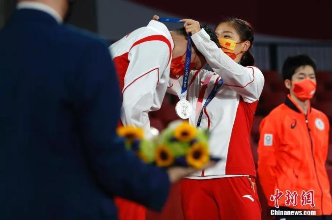 7月26日,东京奥运会决出了乒乓球项目的首枚金牌。在混双决赛中,中国组合许昕/刘诗雯在先胜2局的情况下遭遇逆转,以3:4惜败日本组合水谷隼/伊藤美诚。图为刘诗雯为许昕戴上奖牌。富田 摄