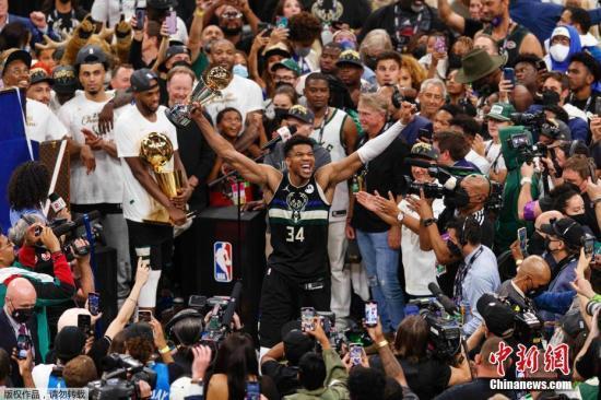 资料图:北京时间7月21日,NBA总决赛第六场在密尔沃基打响,坐镇主场的雄鹿105:98击败太阳,以大比分4:2在系列赛中取得最终的胜利,从而夺得队史自1971年以来的又一个NBA总冠军。图为字母哥拿着MVP奖杯庆祝胜利。