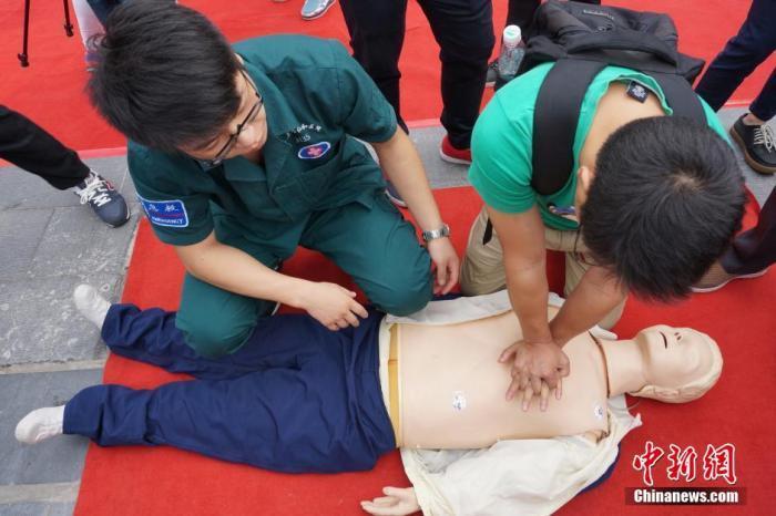 资料图:一位学生在志愿者的帮助下学习心肺复苏术。 董晓斌 摄