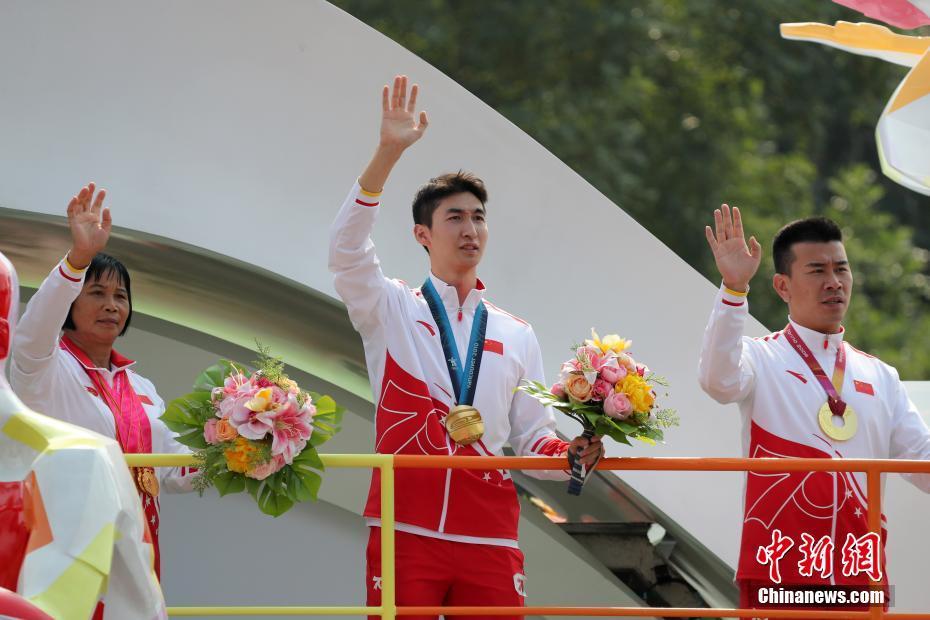资料图:10月1日上午,庆祝中华人民共和国成立70周年大会在北京天安门广场隆重举行。图为群众游行中武大靖(中)挥手致意。中新社记者 韩海丹 摄