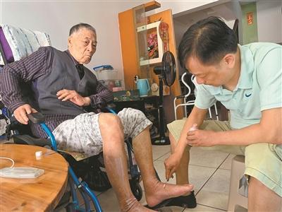 刘沛强为父亲的腿脚擦拭药水。