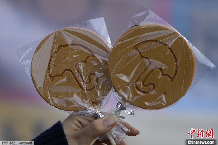 韩国首尔,一名女子在一家商店外拿着捧糖拍照。韩国网飞电视剧《鱿鱼游戏》让椪糖重新流行起来。