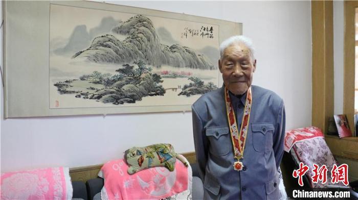 """图为田多麟佩戴""""庆祝中华人民共和国成立70周年纪念章"""" 李晖 摄"""