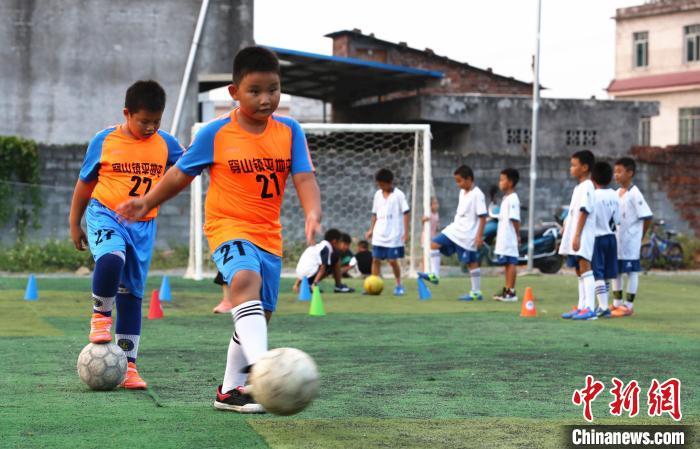 广西柳州市柳江区穿山镇平地屯孩子在进行传球练习。 朱柳融 摄