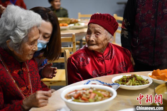 121岁的朱郑氏与百岁老人喻泽琴话家常。 张浪 摄